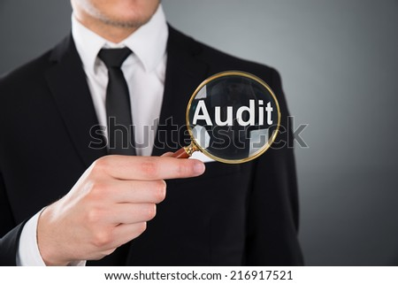 Midsection of young businessman showing Audit word through magnifying glass against gray background - stock photo