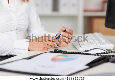 Midsection of young businesswoman holding pen at office desk