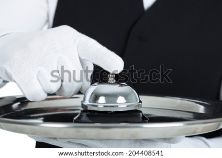 Midsection of young butler holding service bell over white background - stock photo