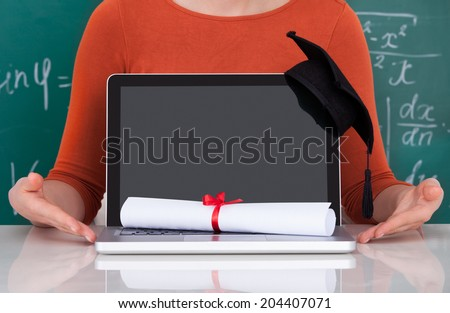 Midsection of young college student showing laptop with mortarboard and degree in classroom - stock photo