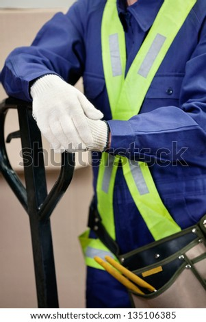 Midsection of young foreman in protective clothing standing in warehouse - stock photo