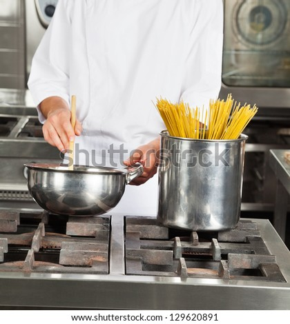Midsection of young male chef cooking food in restaurant kitchen