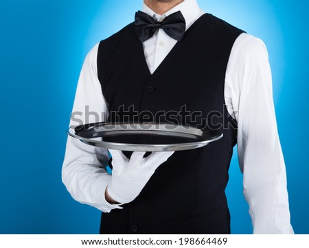 Midsection of young waiter carrying empty tray over blue background - stock photo