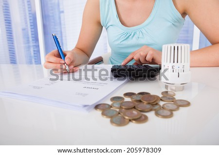Midsection of young woman calculating invoice by coins and thermostat at desk - stock photo