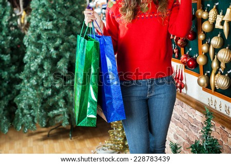 Midsection of young woman carrying shopping bags at Christmas store - stock photo