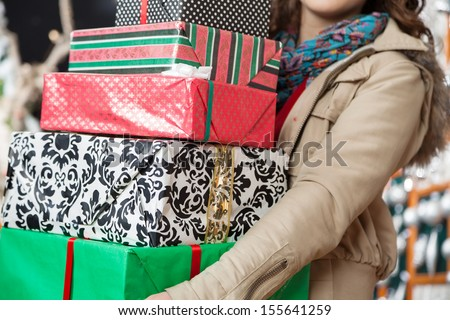 Midsection of young woman carrying stacked Christmas gifts in store