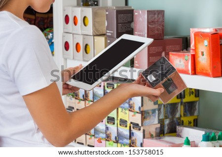 Midsection of young woman scanning barcode through digital tablet at supermarket - stock photo