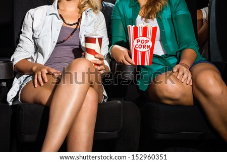 Midsection of young women with popcorn and soda sitting in cinema theater - stock photo