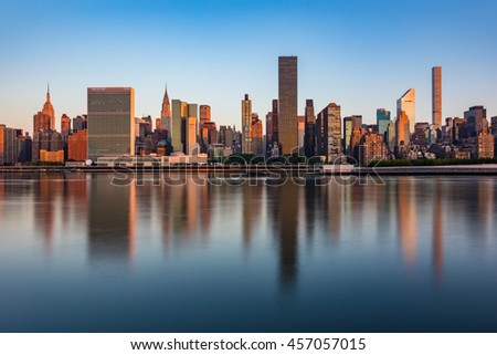 Midtown Manhattan reflections in East River during Sunrise