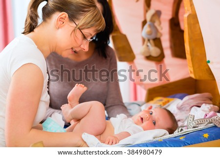 Midwife examining newborn baby at postnatal care in practice