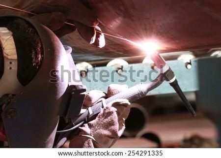 MIG-MAG welder overhead welding big column with mig-mag method - stock photo