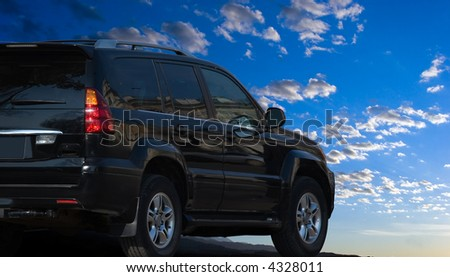 might offroad suv car against bright blue sky - stock photo