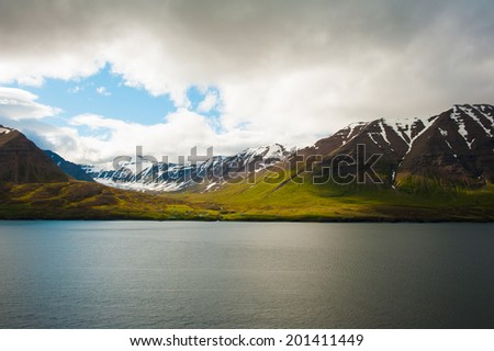Mighty fjords with mountains covered by snow near Olafsfjordur, Northern Iceland - stock photo