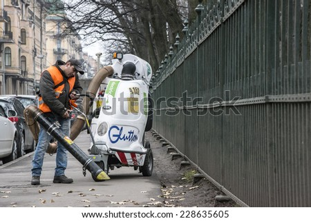 Migrant worker cleaning the Tavricheskaya st., from the leaves, by big vacuum cleaner. Russia, Saint-Petersburg, Tavricheskay st. 05/11/2014  - stock photo