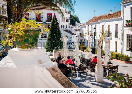 Mijas, Spain- January 5, 2014: Tourists sitting in a sidewalk cafe on central street of Mijas. Mijas is a lovely Andalusian white village on the Costa del Sol. Spain - stock photo