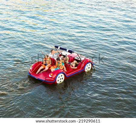 Mikolajki, Poland, August 03, 2014: Family: father, mother, son and daughter on a catamaran. The father is pointing forward. Catamaran is in the shape of a funny toy car. - stock photo