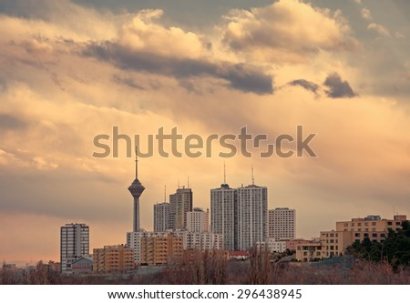 Milad Tower among high rise skyscrapers in the skyline of Tehran at dusk. - stock photo