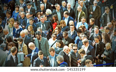 MILAN - APRIL 10: People background, a crowd of persons entering Salone del Mobile, international home furnishing design and accessories exhibition on April 10, 2013 in Milan, Italy.  - stock photo
