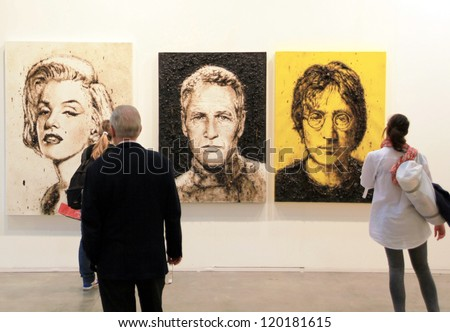 MILAN - APRIL 08: People look at paintings representing Monroe, Newmann and Lennon during MiArt, international exhibition of modern and contemporary art on April 08, 2011 in Milan, Italy - stock photo