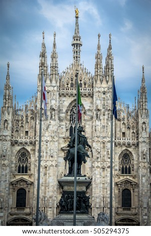 Milan cathedral exterior with Italian flagpoles and statue