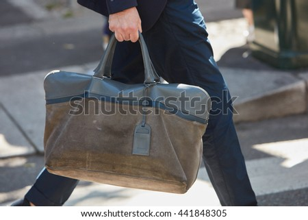 MILAN - FEBRUARY 20: Man poses for photographers with brown green leather bag before Emporio Armani fashion show, Milan Men's Fashion Week street style on June 20, 2016 in Milan. - stock photo