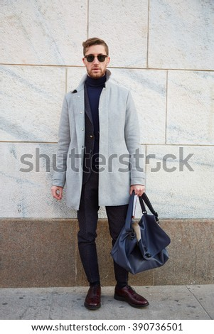 MILAN - FEBRUARY 25: Man poses for photographers with gray coat before Cristiano Burani fashion show, Milan Fashion Week Day 2 street style on February 25, 2016 in Milan.