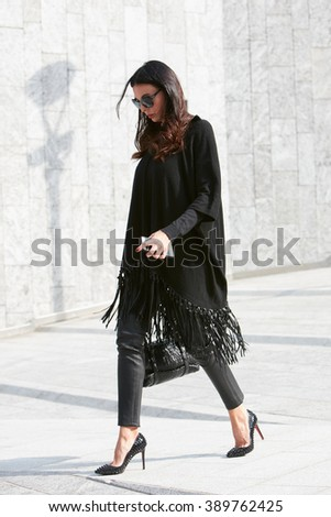 MILAN - FEBRUARY 24: Woman in black clothing and Louboutin shoes before Simonetta Ravizza fashion show, Milan Fashion Week Day 1 street style on February 24, 2016 in Milan. - stock photo