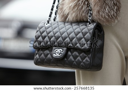 MILAN - FEBRUARY 27: Woman poses for photographers before Emporio Armani show with Chanel bag Milan Fashion Week Day 3, Fall/Winter 2015/2016 street style on February 27, 2015 in Milan. - stock photo