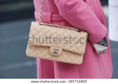 MILAN - FEBRUARY 25: Woman poses for photographers with beige Chanel bag and pink coat before Costume National fashion show, Milan Fashion Week Day 2 street style on February 25, 2016 in Milan. - stock photo