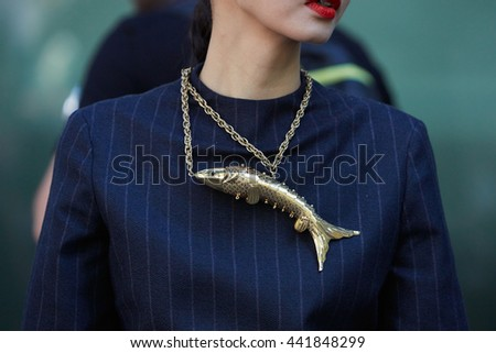 MILAN - FEBRUARY 20: Woman poses for photographers with golden fish necklace before Emporio Armani fashion show, Milan Men's Fashion Week street style on June 20, 2016 in Milan. - stock photo