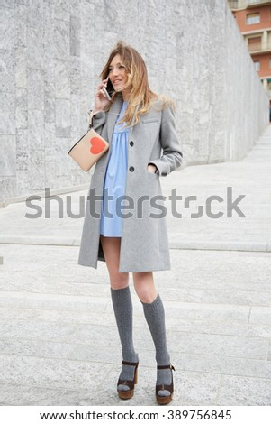 MILAN - FEBRUARY 25: Woman poses for photographers with gray coat and bag with heart before Costume National fashion show, Milan Fashion Week Day 2 street style on February 25, 2016 in Milan. - stock photo