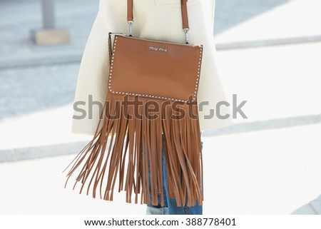 MILAN - FEBRUARY 24: Woman poses for photographers with leather Miu Miu bag with fringes before Simonetta Ravizza fashion show, Milan Fashion Week Day 1 street style on February 24, 2016 in Milan. - stock photo