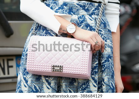 MILAN - FEBRUARY 24: Woman poses for photographers with pink bag and Daniel Wellington watch before Gucci fashion show, Milan Fashion Week Day 1 street style on February 24, 2016 in Milan. - stock photo