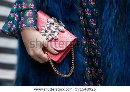 MILAN - FEBRUARY 26: Woman poses for photographers with pink jewel bag and blue fur before Etro and Iceberg fashion show, Milan Fashion Week Day 3 street style on February 26, 2016 in Milan.