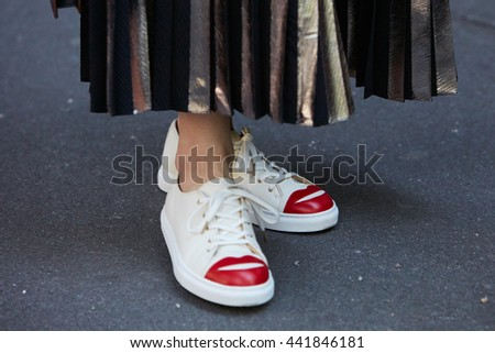 MILAN - FEBRUARY 20: Woman poses for photographers with red mouth white shoes before Emporio Armani fashion show, Milan Men's Fashion Week street style on June 20, 2016 in Milan.