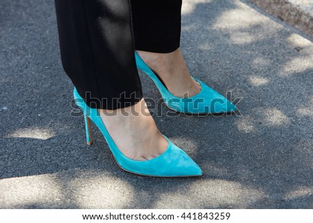 MILAN - FEBRUARY 20: Woman poses for photographers with turquoise high heel shoes before Etro fashion show, Milan Men's Fashion Week street style on June 20, 2016 in Milan.
