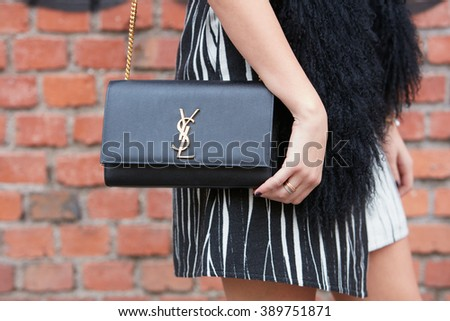 MILAN - FEBRUARY 25: Woman poses for photographers with Yves Saint Laurent black leather bag before Fendi fashion show, Milan Fashion Week Day 2 street style on February 25, 2016 in Milan. - stock photo