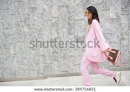 MILAN - FEBRUARY 25: Woman poses walking with pink suit and Louis Vuitton bag before Costume National fashion show, Milan Fashion Week Day 2 street style on February 25, 2016 in Milan. - stock photo
