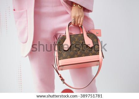 MILAN - FEBRUARY 25: Woman poses with pink and brown Louis Vuitton bag and pink suit before Costume National fashion show, Milan Fashion Week Day 2 street style on February 25, 2016 in Milan. - stock photo
