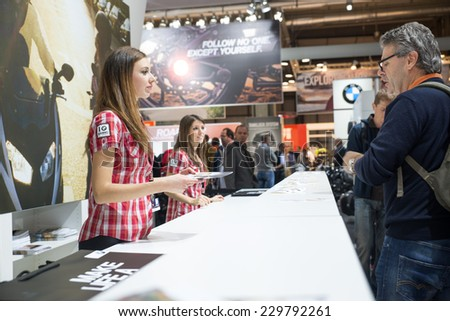 MILAN, IT. NOVEMBER 5, 2014. Hostess giving fliars at bmw motorrad stand at EICMA 2014.BMW Motorrad is the motorcycle brand of the German company BMW. - stock photo