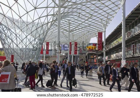 MILAN, ITALY - APRIL 15 2015: Architectural view of the covered glass roof of Fiera Milano, during Salone del Mobile fair in Milan, with people around