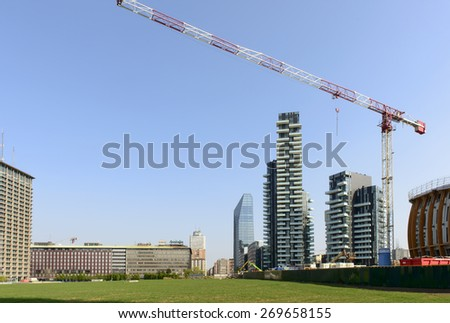 MILAN, ITALY - APRIL 11: building site cranes and of tall buildings at business hub prospecting on the wheat field prepared for EXPO 2015 in city center, shot  on april 11 2015  Milan, Italy  - stock photo