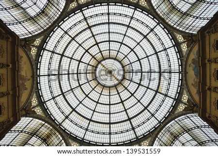 MILAN, ITALY - APRIL 30: Glass roof of Vittorio Emmanuele II shopping gallery on April 30, 2013 in Milan, Italy. Built in 1875 this gallery is one of the most popular shopping areas in Milan. - stock photo