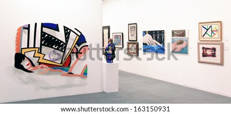 MILAN, ITALY - APRIL 08: Looking at aintings galleries during MiArt, international exhibition of modern and contemporary art on April 08, 2011 in Milan, Italy  - stock photo