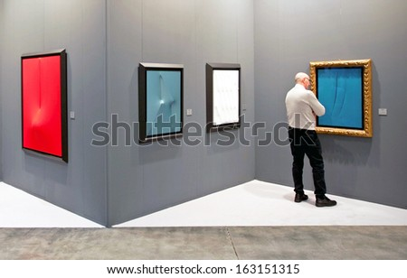 MILAN, ITALY - APRIL 08: Man looks at paintings galleries during MiArt, international exhibition of modern and contemporary art on April 08, 2011 in Milan, Italy  - stock photo
