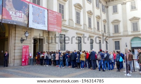 MILAN, ITALY - APRIL 12, 2014: People lining up at the Palazzo Reale entrance in Milan. The Royal Palace was the seat of Milan's government for many centuries but today is an important cultural centre - stock photo