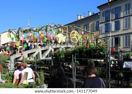 MILAN, ITALY - APRIL 14: People look for flowers during the annual Flowers Market in the fashion and culture Navigli area April 14, 2013 in Milan, Italy.