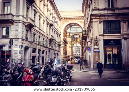 MILAN, ITALY - April 9, 2014: People walk on the street near Galleria Vittorio Emanuele II shopping mall in Milan. Toned picture - stock photo