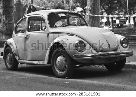 MILAN, ITALY-AUGUST 9, 2014: German motor car Volkswagen Beetle Parked in the city black and white. - stock photo