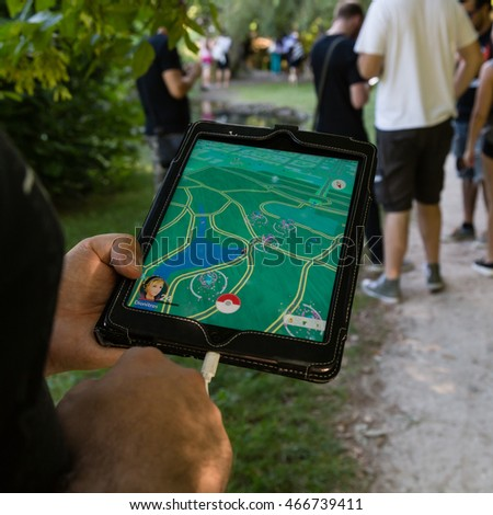 MILAN, ITALY - AUGUST 7, 2016: Hundreds of young people meet in a city park and take part in the Pokemon Go Tour, official event for hunting and catching Pokemons.